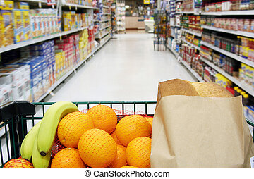 Grocery cart loaded with fresh fruit and bread moving...