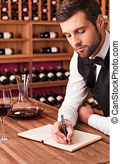 Making notes about wine Confident male