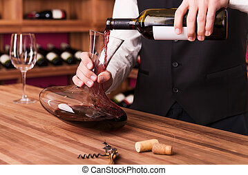 Sommelier at work Confident male sommelier pouring wine to...