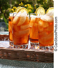 Ice tea - Glasses of refreshing lemon ice tea, outside in...