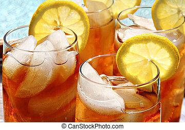 Ice tea - Four glasses of lemon ice tea, outside by the...