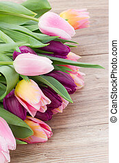 pink tulips on wooden table