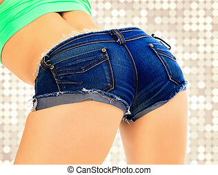 Female ass in blue jeans shorts, abstract background