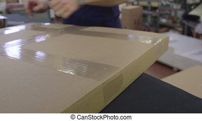 Employee taping box for shipping in a plant