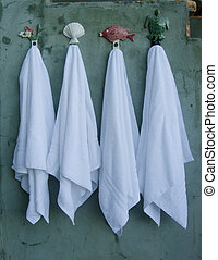 Four Towels Hang on Decorative Hooks - Four crisp white...