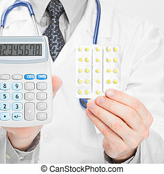 Doctor holdling calculator and pills in hands - studio shot