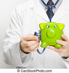 Doctor checking piggybank with help of stethoscope