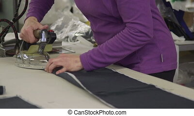 Employee ironing fabric for sofas in a plant