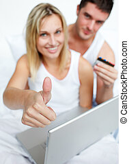 Couple in bed buying on-line successfully - Couple buying...