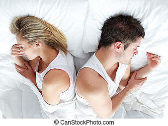 Sad and angry couple lying in bed separately. Marriage trouble