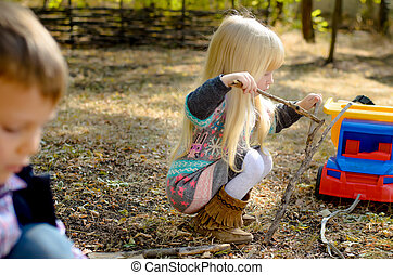 Little Blond Girl Playing Sticks on the Ground - Side View...