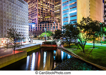 Buildings and pond at Thanks-Giving Square at night in...