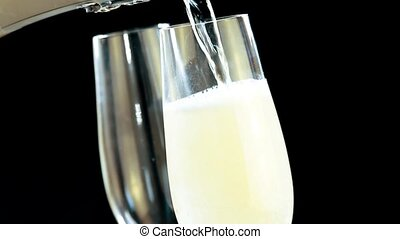 champagne into flutes on black - pouring champagne into...