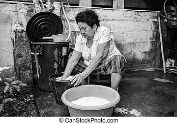 Senior asian woman washing cloths by hand - Black and white...
