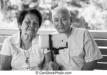 Happy senior couple posing for a selfie - Black and white...