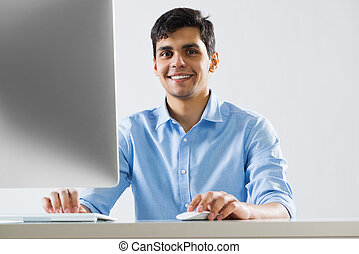 Man at work - Young man sitting at desk and working on...