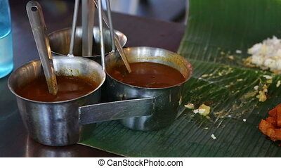 man pours out dressings onto Indian food on banana leaf -...