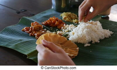 man eats food with hands from banana leaf - white man eats...