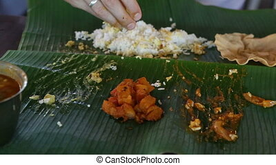man eats rice with flat cake from banana leave - white man...