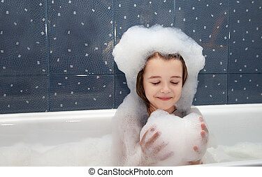 little girl playing with soap suds in a bath closeup