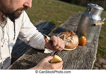 bearded hermit eating cheese and bread in the nature -...