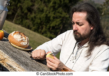 man snacking healthy food in the nature - long-haired man...