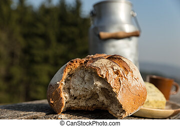 rustically bread and milk churn on a wooden table - a...