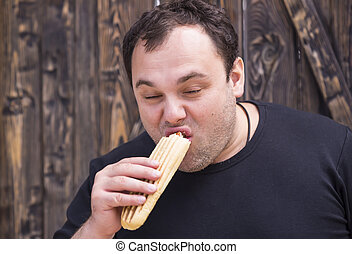 man eating a hot dog