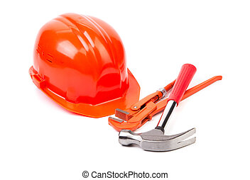 Red safety helmet and adjustable pipe wrench Isolated on a...