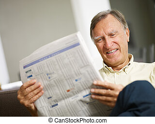 Senior man reading stock listings and smiling Copy space