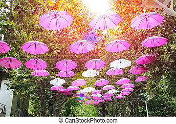 Pink and white umbrellas decorate streets in the resort town...