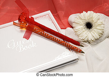 Guest Book - White and silver guest book with pens at a...