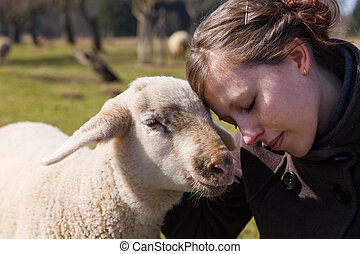 pretty young woman leaning head on sweet lamb