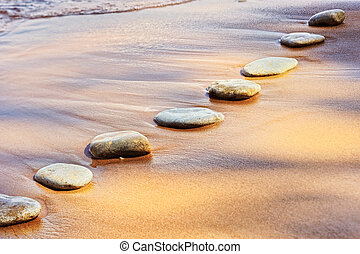 Stones and Sand - Consecutive series of boulders on a sandy...