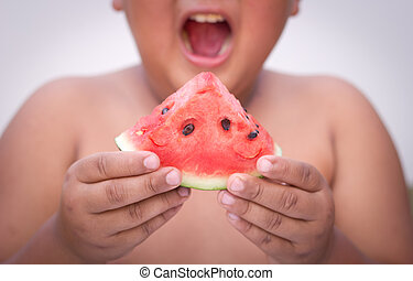 Asian boy holding out a sliced water melon
