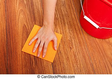 Floor cleaning - Womans hand cleaning the floor with yellow...