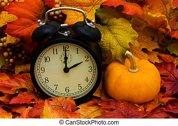 Daylight savings - Fall coloured leaves with a black clock,...