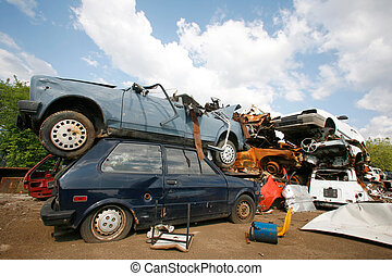car junkyard - Cars piled on top of each other in junkyard