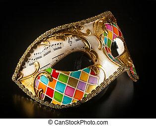 Venetian mask harlequin style isolated on black background.