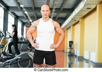 Young athletic man smiling on gym