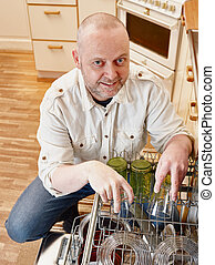 Man and dishwasher - Homeworks, smiling man to fill the...