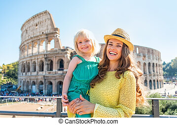 Portrait of happy mother and baby girl in front of colosseum...