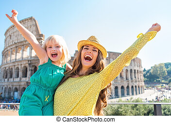 Happy mother and baby girl rejoicing in front of colosseum...