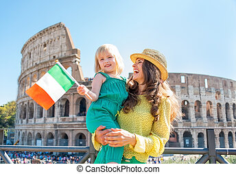 Happy mother and baby girl with italian flag in front of...