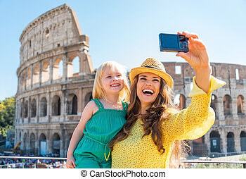 Happy mother and baby girl making selfie in front of...