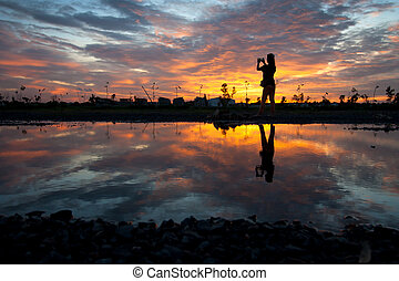 silhouette women at sunset - silhouette women and reflection...