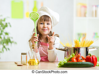 Kid cook makes healthy vegetables meal in the kitchen - Kid...