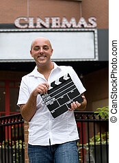 At the Movies - A young man or movie critic holding a movie...