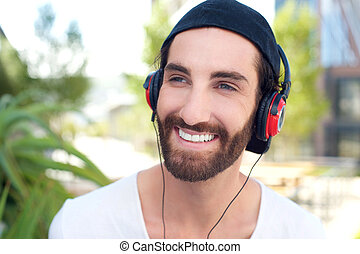 Happy young man smiling with headphones outdoors