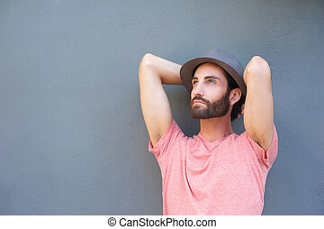 Young man relaxing with hands behind head